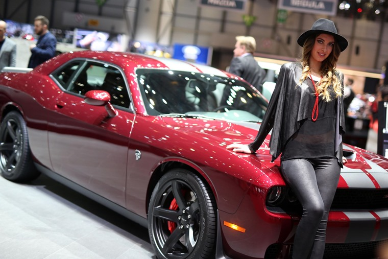 A glamour model poses with a Dodge Challenger.