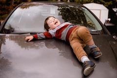 photo-of-boy-lying-down-on-car-hood-3204087